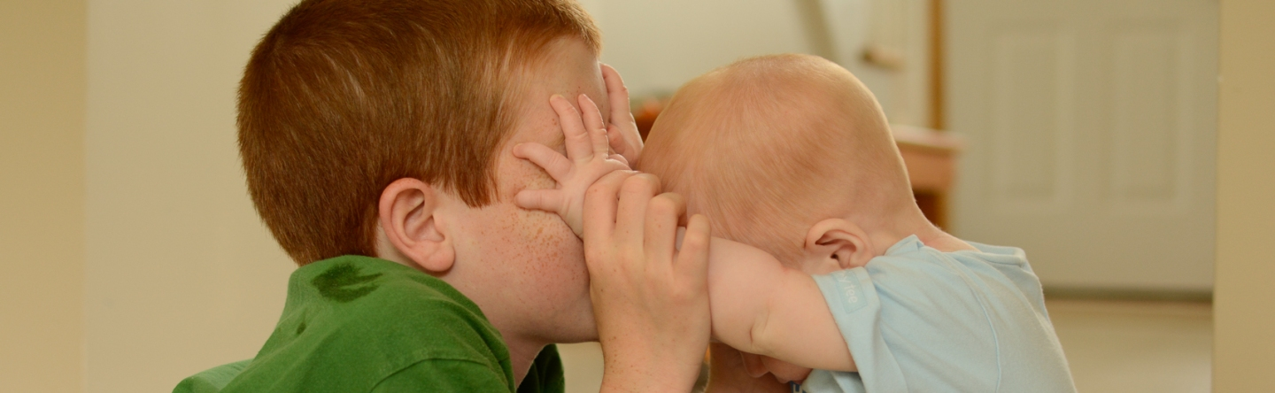 Baby touching brother's eyes