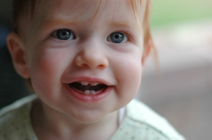 Infant smiling with blue eyes