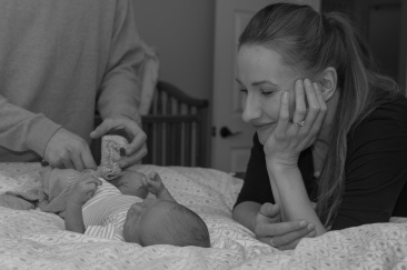 Mom leaning over newborn in Albany NY documentary photograph