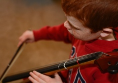 Documentary photography close up of boy playing cello