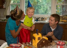 Toddler with party hat eating cake
