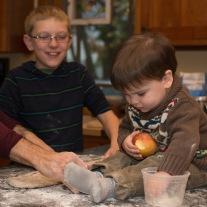 Toddler reaching into flour bowl