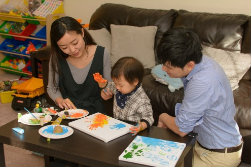 Documentary family photograph of parents helping toddler paint handprints