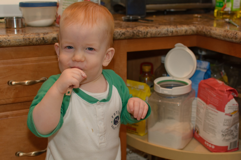 Toddler sucking on teaspoon of sugar