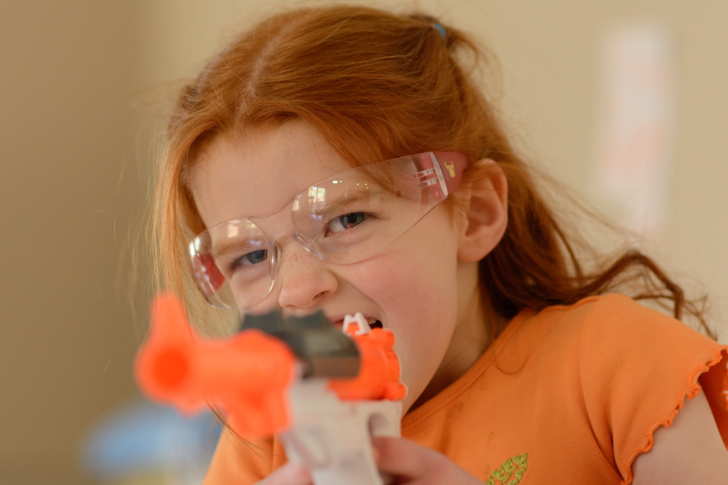 girl pointing nerf gun at camera