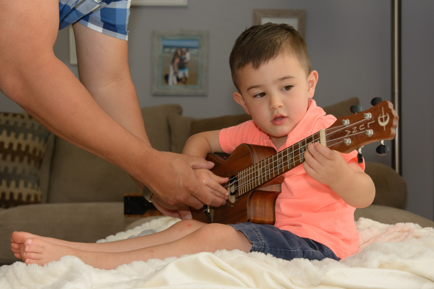 Dad showing boy hold to play ukelele
