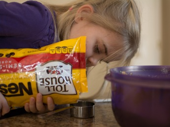 Girl pouring chocolate chips into cup