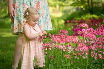 Young girl picking flowers with mom