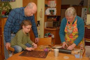 Grandma and Grandpa making cookies with granddaughter