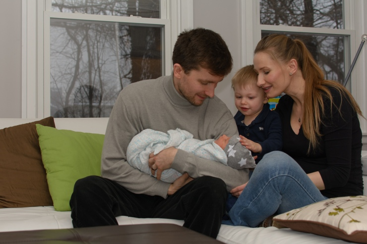 Mom, Dad, and brother looking at newborn