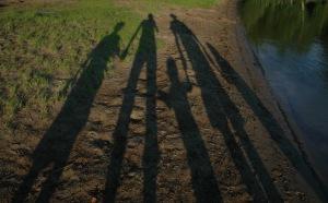 Shadows of family along a lake shore