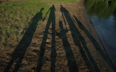 Shadows of family along a lake shore