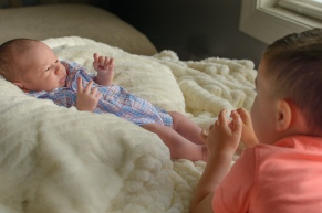 Toddler touching baby's toes