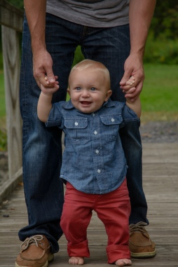 Toddler walking with Dad's help