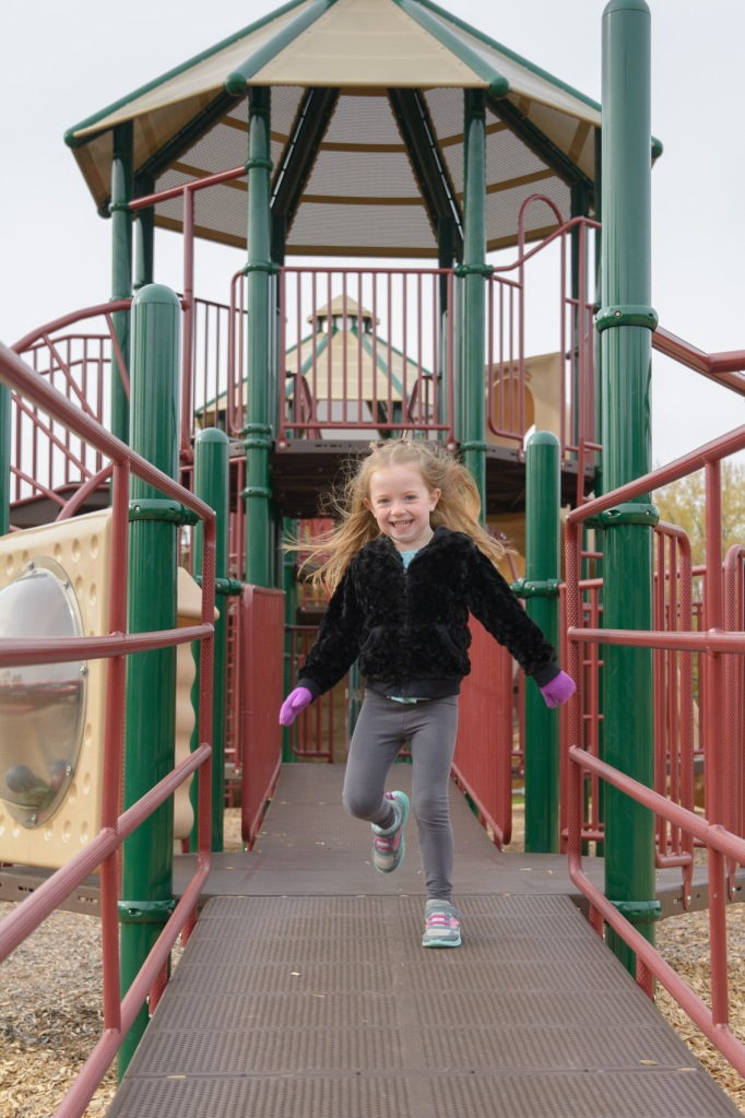 Girl running down playground ramp