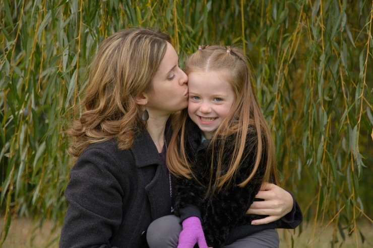 Mom kissing daughter's cheek