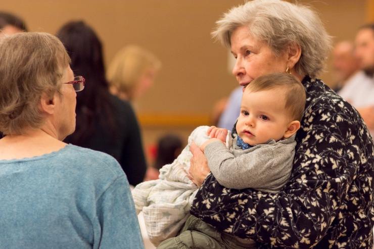 Grandma holding baby during wedding reception