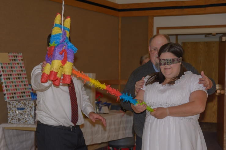 Blindfolded bride ready to hit pinata