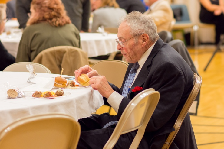 Elderly father eating refreshments during wedding reception