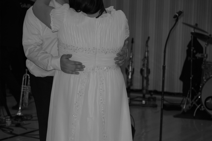 Details of bride's wedding dress while dancing