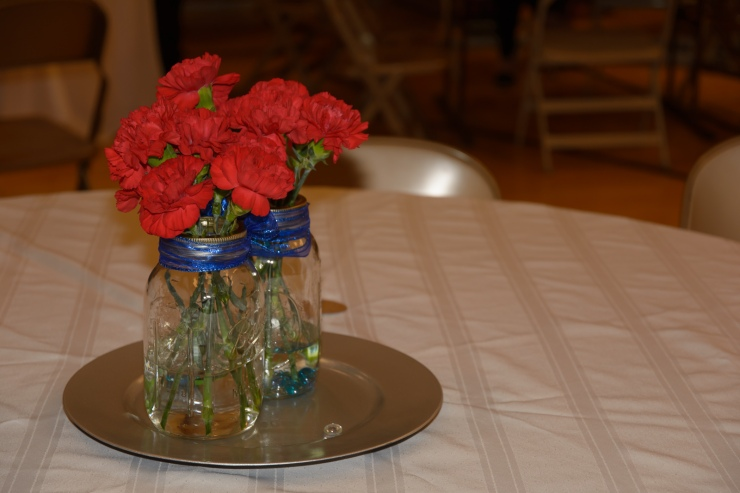 Red carnations in mason jars as wedding reception center pieces