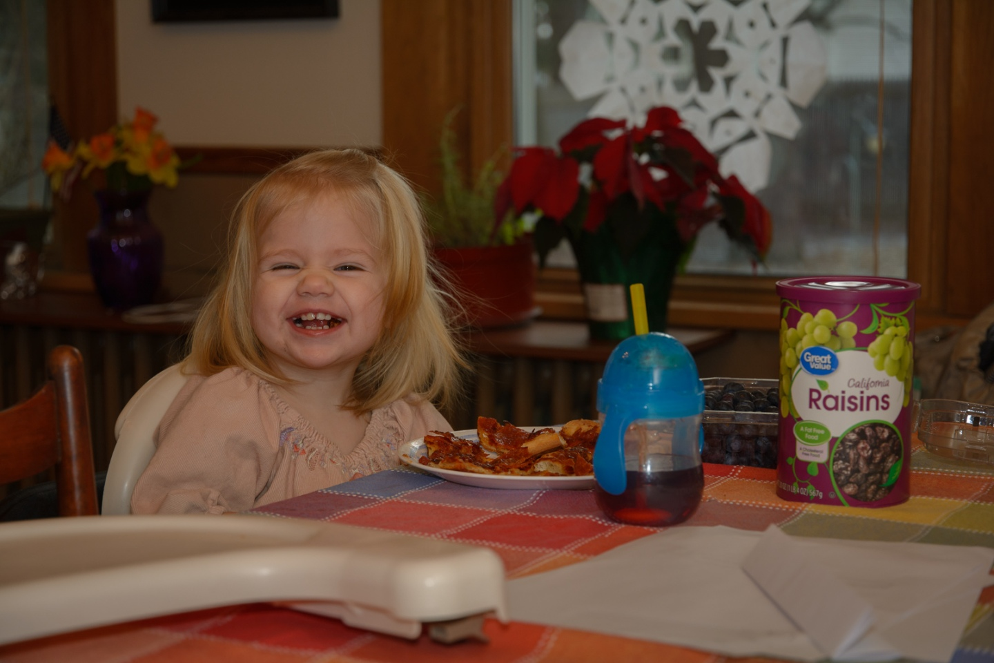 Smiling toddler sitting at table in-home documentary photogaph
