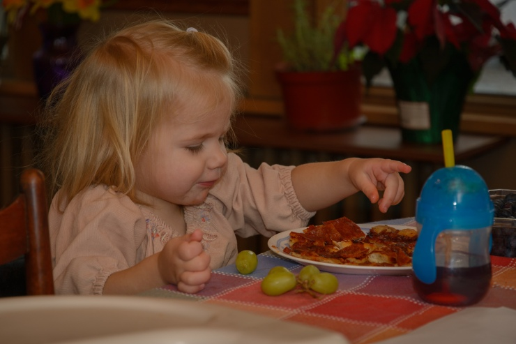 Toddler eating pizza in her home near Scotia NY