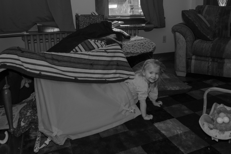 Little girl poking head out of blanket fort