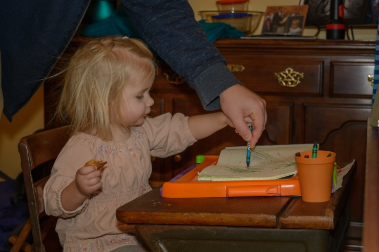 Toddler drawing with crayons on a desk with her Dad helping