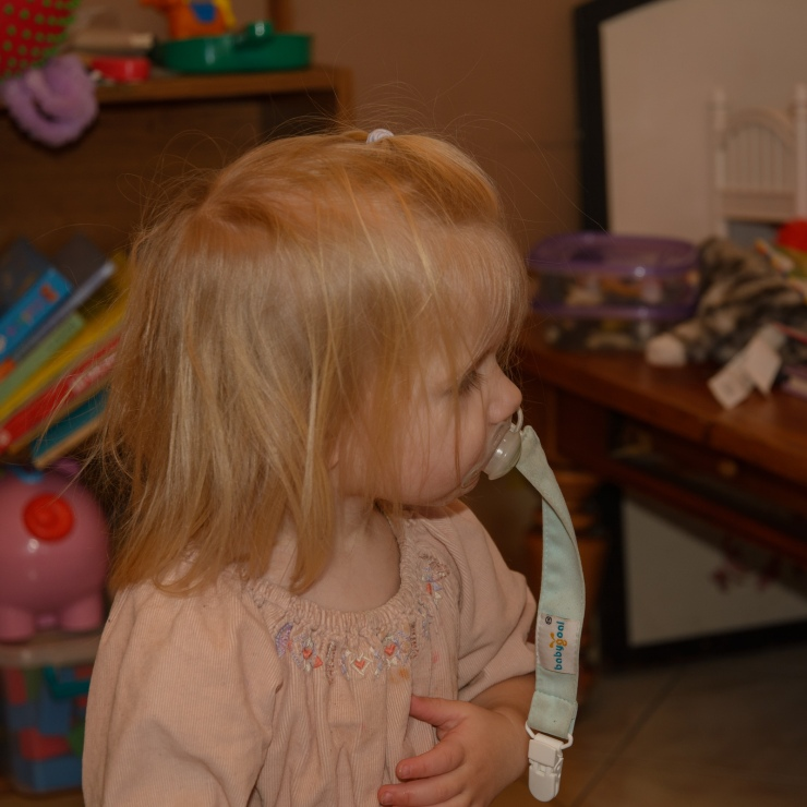 Blond toddler with pacifier in mouth