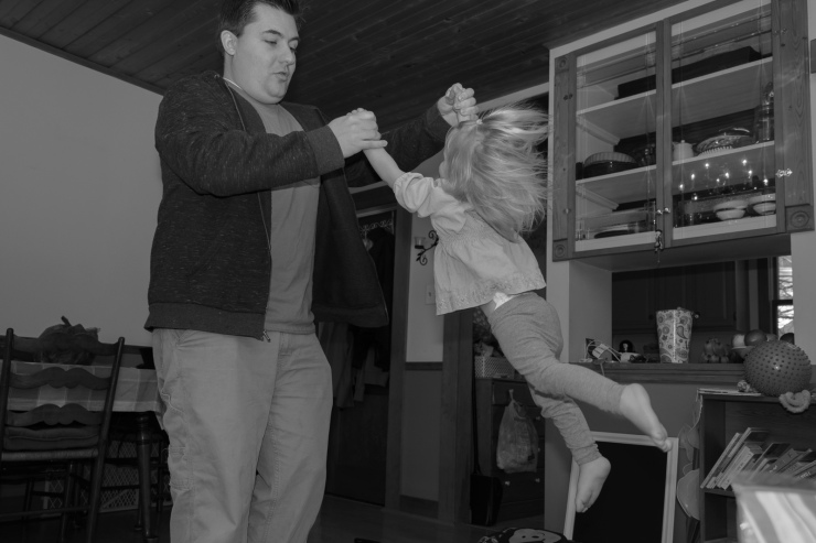 Black and white in home photography of dad swinging a toddler