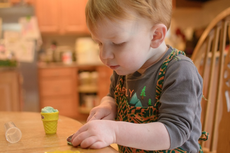 Toddler playing with playdoh at the table