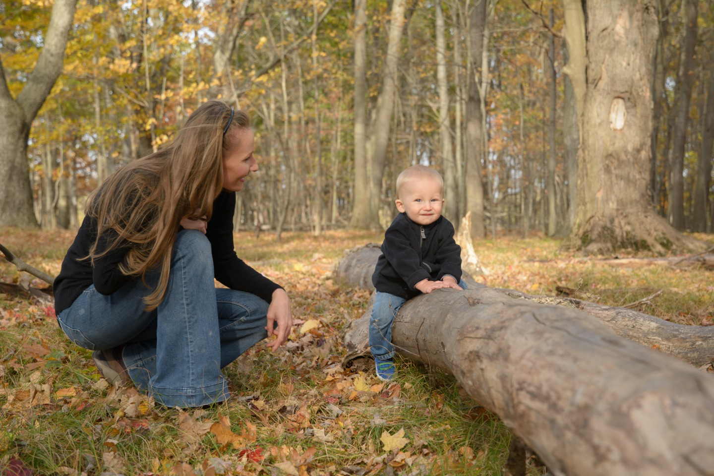 Mother and son in woods with son on fallen tree