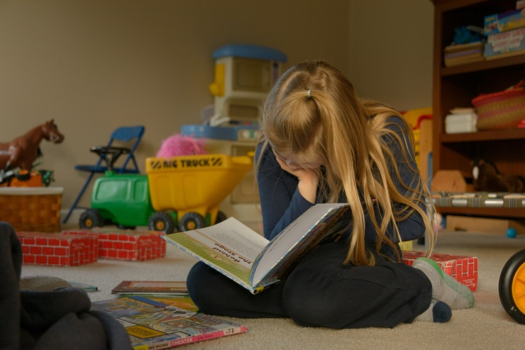 Girl reading book in playroom