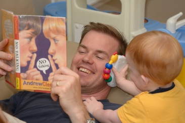 Dad reading a book while toddler holds his phone