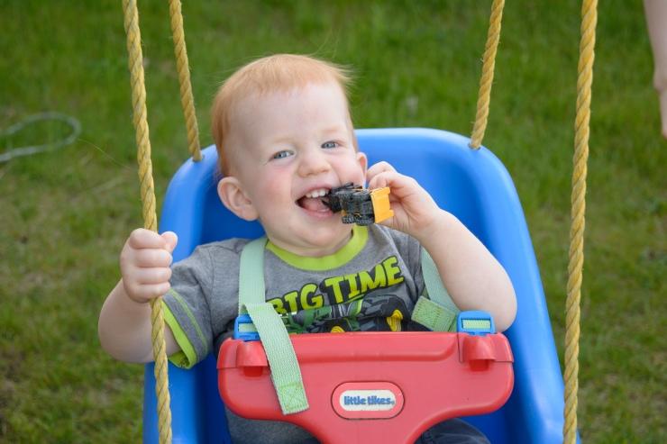 Toddler smiling while swinging