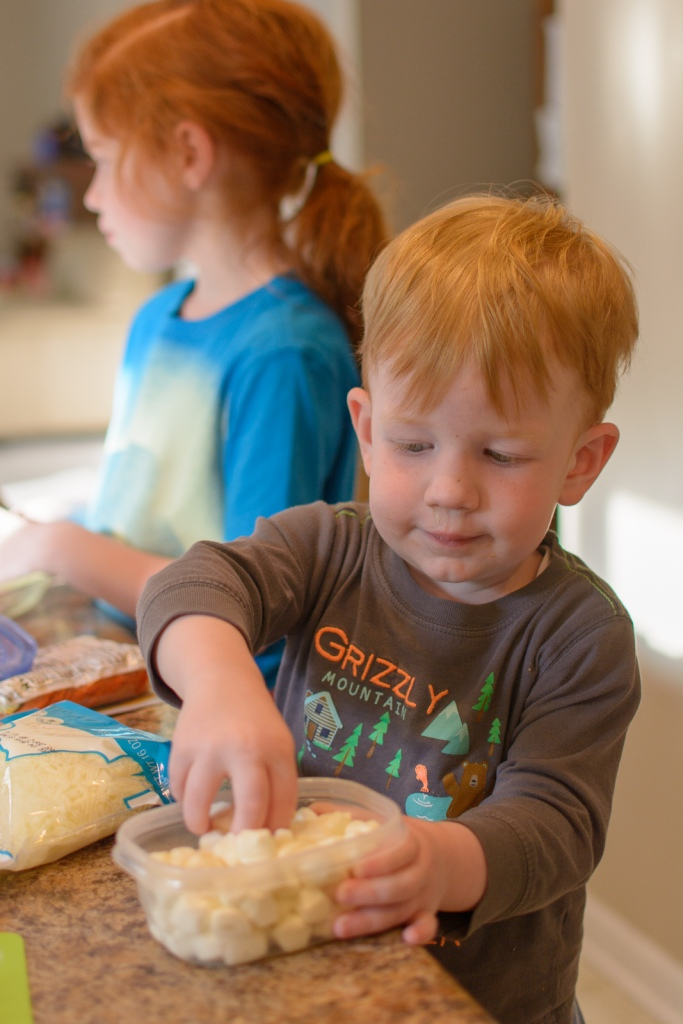 Toddler teaching into mozerella cheese container