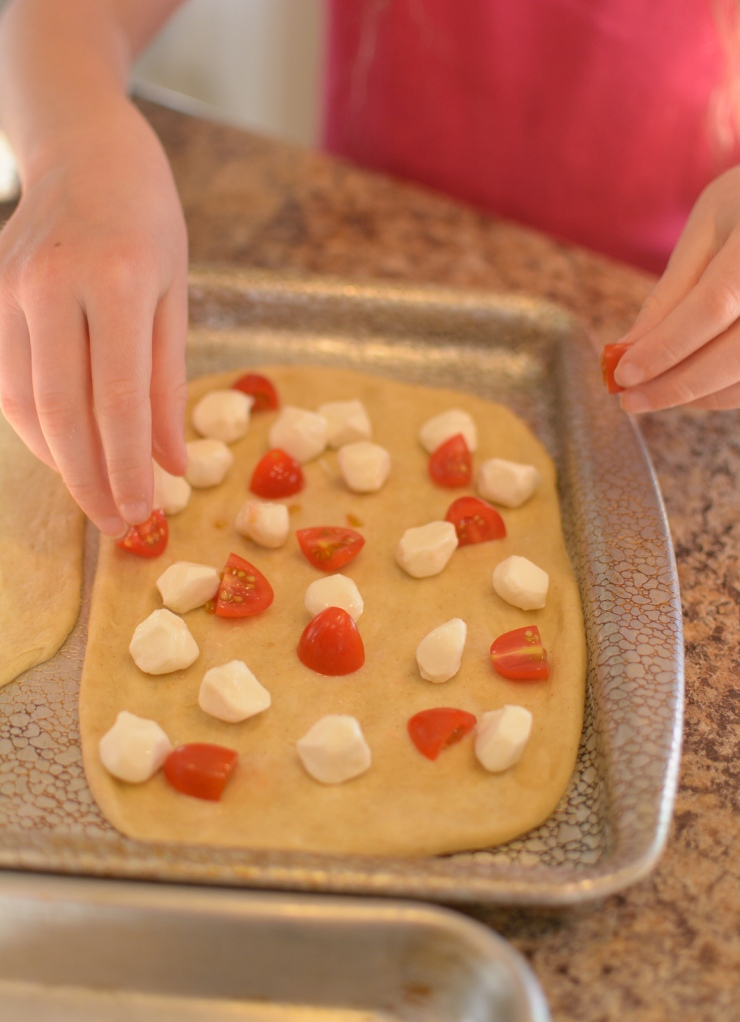 Girl spreading mozerella cheese and tomatoes on dough