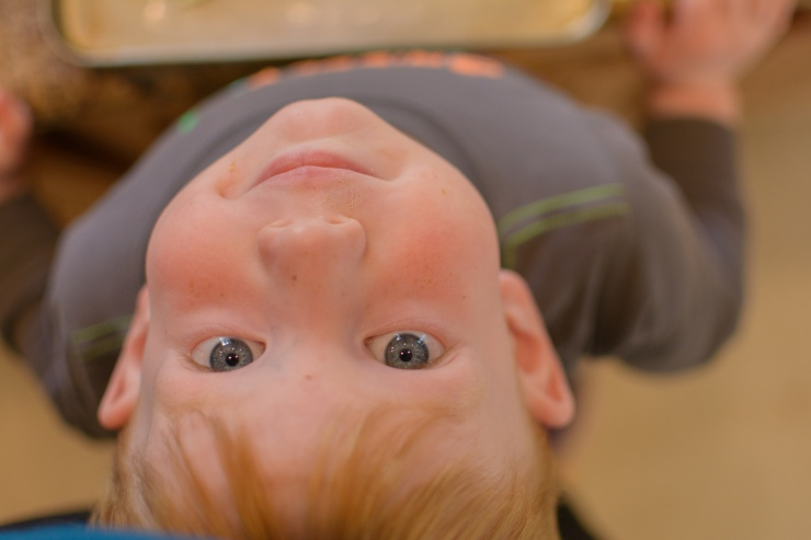 Upside down toddler smiling at camera