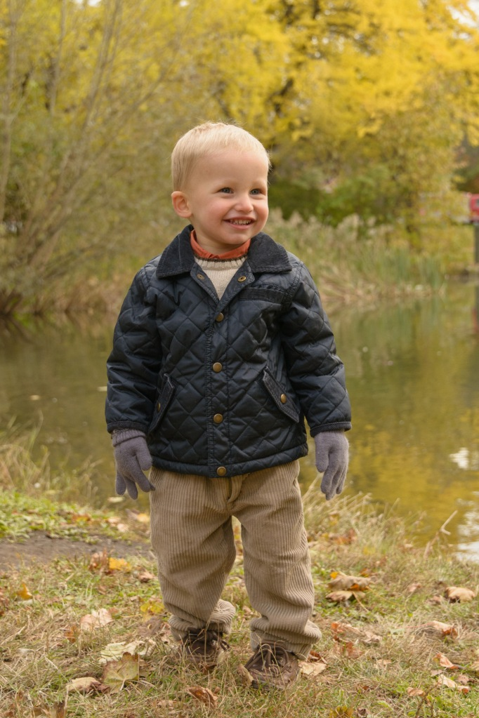 Toddler smiling by pond
