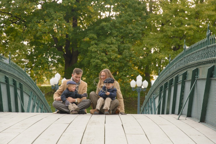 Family sitting on bridge