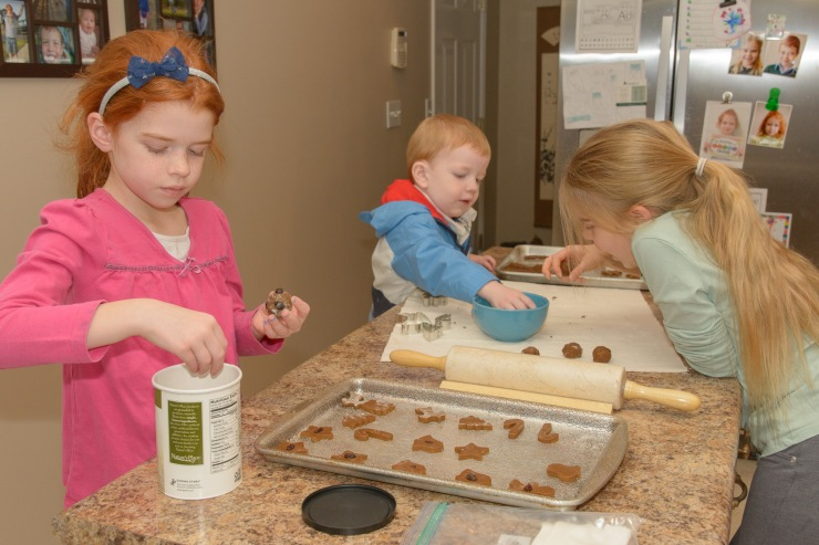 Three kids making gingerbread cookies