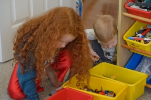Toddler and girl looking into lego bin
