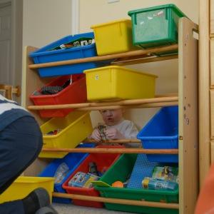 Preschooler hiding behind a bin of toys