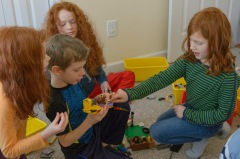 Three girls surrounding a boy and his lego creation