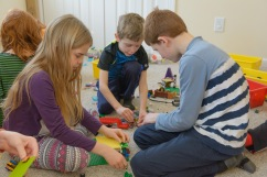 Three kids examining a lego house
