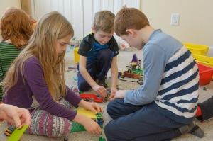 Three kids examining a lego house