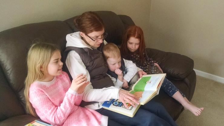 Mom reading to three children