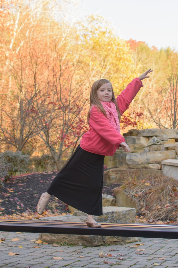 Girl demonstrating ballet pose outside