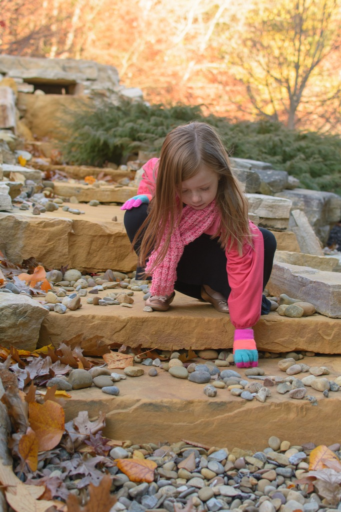 Young girl picking up rocks outside